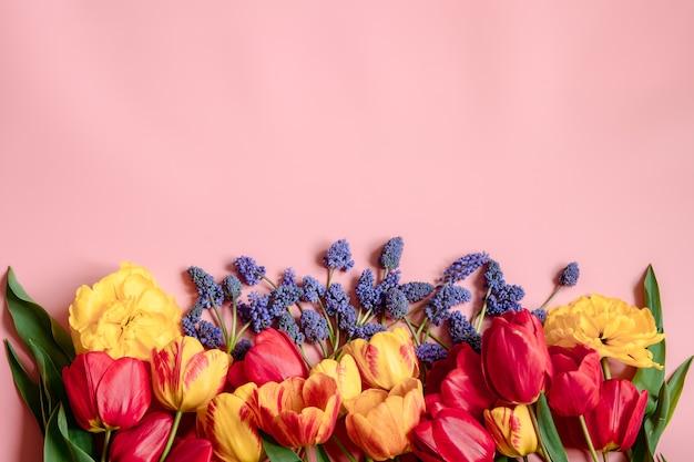 Kreatywna wiosenna kompozycja z rozłożonymi na powierzchni kwiatami muscari i tulipanami.