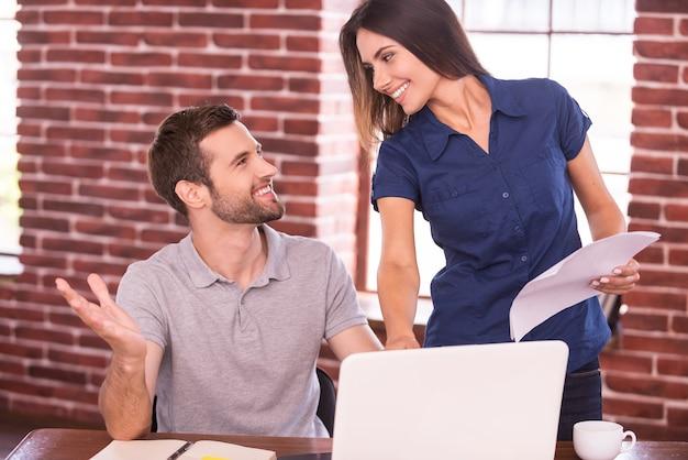 Kreatywna współpraca. wesoły młody człowiek siedzi w swoim miejscu pracy i gestykuluje, podczas gdy piękna kobieta stoi blisko niego i uśmiecha się
