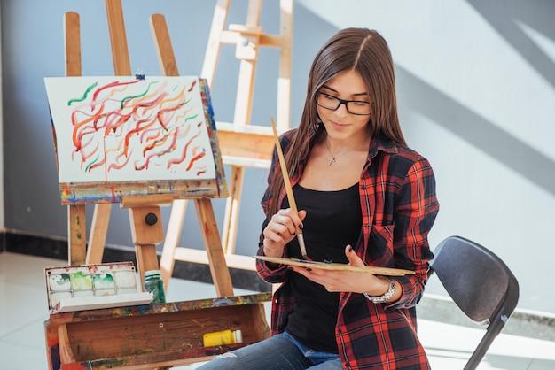 Kreatywna zadumana malarz dziewczyna maluje kolorowy obraz na płótnie kolorami olejnymi w warsztacie.