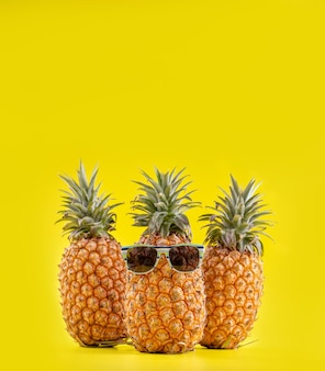Kreatywne ananasy z okularami przeciwsłonecznymi na białym tle na żółtym tle, wzór projektu letnich wakacji na plaży, miejsce na kopię, z bliska, puste dla tekstu