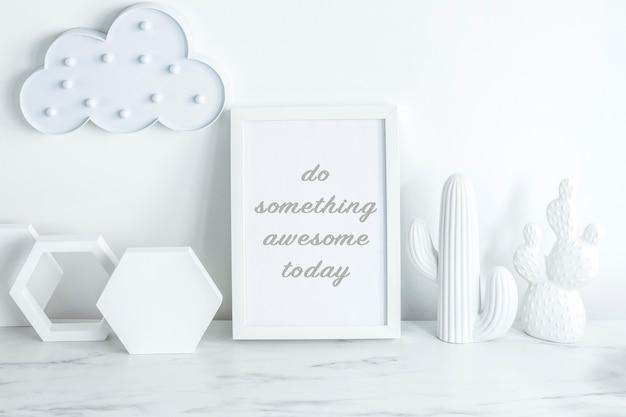 Kreatywne biurko w skandynawskim stylu z białą makietą, chmurką na białej ścianie, dodatkami o geometrycznych kształtach i białymi figurkami kaktusów. biała minimalistyczna koncepcja.
