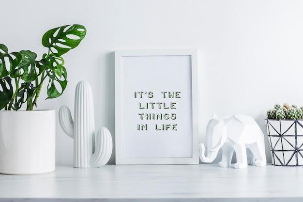 Kreatywne biurko w skandynawskim stylu z białą makietą, kaktusy w hipsterskiej doniczce, roślina w klasycznej doniczce, białe figurki kaktusów i słonia. biała minimalistyczna koncepcja.
