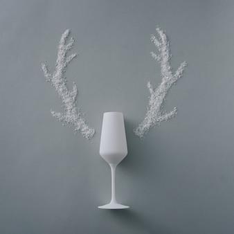 Kreatywne boże narodzenie tło z szampanem flet i poroże renifera createdof sztucznego śniegu zimowego na srebrnym tle rey z copyspace