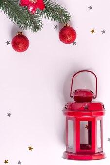 Kreatywne bożonarodzeniowe mieszkanie leżało ze staromodną latarnią i gałązkami jodły ozdobionymi błyszczącymi czerwonymi kulkami na szaro