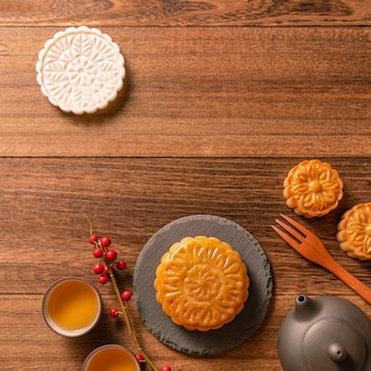 Kreatywne ciasto księżycowe projekt stołu mooncake - chińskie tradycyjne ciasto z filiżankami do herbaty, koncepcja święta środka jesieni, widok z góry, układanie na płasko.