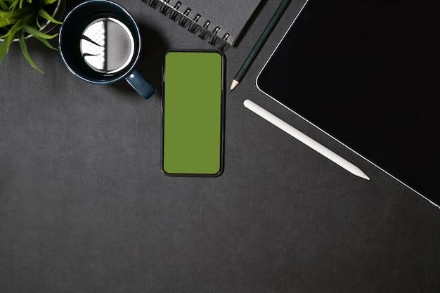 Kreatywne ciemne skórzane biurko z tabletem, obiektywem i designerskim gadżetem