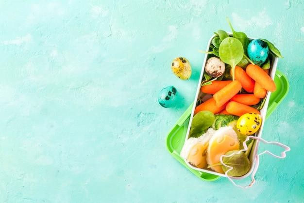 Kreatywne dziecięce pudełko śniadaniowe na wielkanoc, kanapki z serem, świeże warzywa - ogórki, marchew, szpinak, kolorowe jajka przepiórcze. jasnoniebieski stół, widok z góry miejsca kopiowania