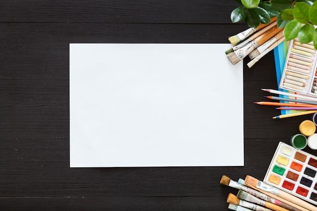 Kreatywne farby tło dostarcza pędzle papierowe paintbox na czarnym drewnianym biurku
