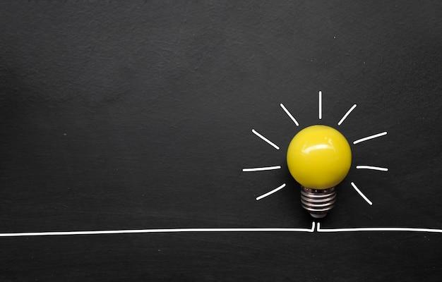Kreatywne inspiracje, pomysły, koncepcje. żarówka na tle tablicy. widok z góry