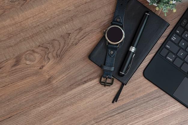 Kreatywne miejsce do pracy z czarną klawiaturą komputerową, smartwatchem, notatnikiem i długopisem na drewnianym blacie, widok z góry, miejsce na kopię.