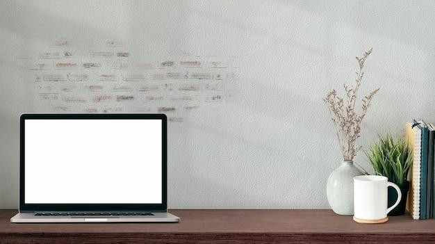 Kreatywne miejsce do pracy z pustym ekranem laptopa, kubkiem, ceramicznym wazonem i książkami