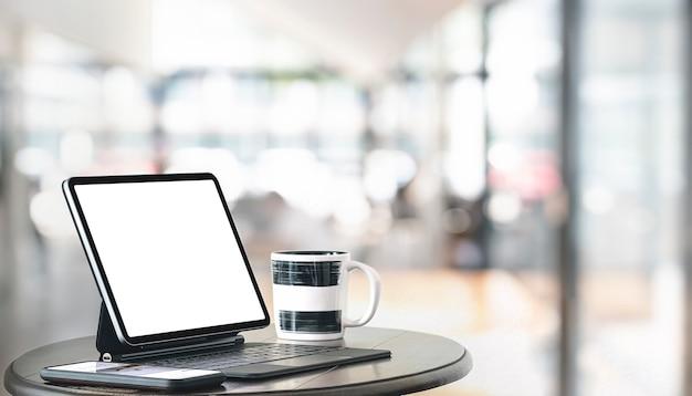 Kreatywne miejsce do pracy z tabletem i klawiaturą na drewnianym stoliku kawowym