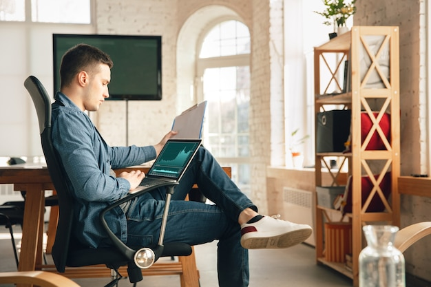 Kreatywne miejsce pracy - zorganizowana przestrzeń do pracy tak, jak lubisz dla inspiracji. mężczyzna pracujący w biurze w wygodnym stroju, zrelaksowanej pozycji i bałaganiarskim stole. wybierz odpowiednią atmosferę - idealnie przejrzystą lub chaosową.