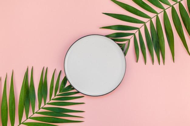 Kreatywne mieszkanie leżało z góry na zielone tropikalne liście palmowe z pustym talerzem