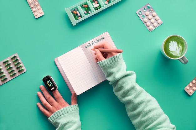 Kreatywne mieszkanie leżało z notatnikiem, aby dotrzymać harmonogramu medycznego. ręce z piórem i pulsoksymetrem. różne pigułki i futerał na tabletkę na zielonym miętowym pastelowym stole. monitorowanie, kiedy należy przyjmować różne tabletki lub witaminy.