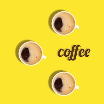 """Kreatywne mieszkanie leżało z trzema filiżankami czarnej kawy espresso i słowem """"kawa"""" na żółtym"""