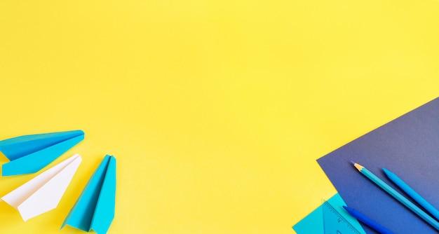 Kreatywne, modne, minimalistyczne, szkolne lub biurowe miejsce do pracy z niebieskimi materiałami na żółtym
