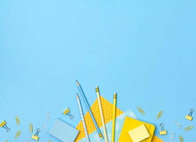 Kreatywne, modne, minimalistyczne, szkolne lub biurowe miejsce do pracy z żółtymi i niebieskimi materiałami eksploatacyjnymi