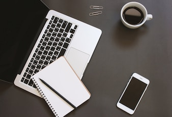Kreatywne płaskie zaprojektowanie miejsca pracy biurko z laptopa, notebooka, smartfona i kawy z miejsca na kopię tła
