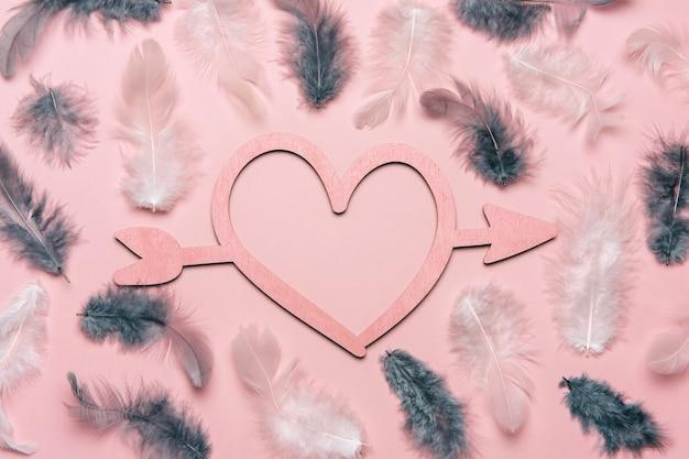 Kreatywne płaskie drewniane serce na różowo z naturalnym piórkiem.