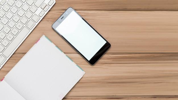 Kreatywne płaskie położenie drewnianego biurka w miejscu pracy z klawiaturą i telefonem