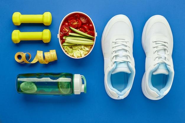 Kreatywne płaskie rozmieszczenie sprzętu sportowego i fitness. białe tenisówki damskie, butelka wody, hantle, miarka i pudełko na drugie śniadanie ze zdrową sałatką warzywną.