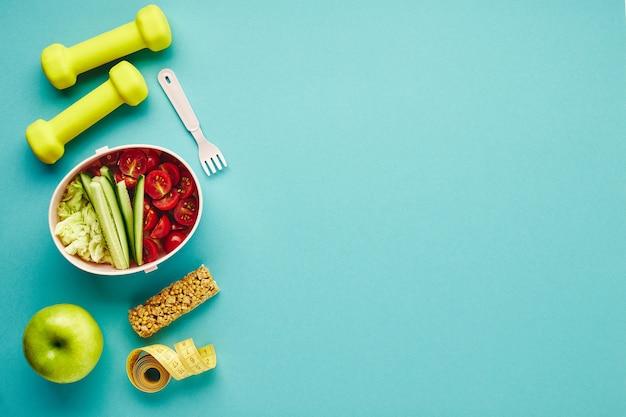 Kreatywne płaskie rozmieszczenie sprzętu sportowego i fitness. hantle, miarka i pudełko na drugie śniadanie ze zdrową sałatką warzywną