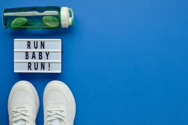 Kreatywne płaskie rozmieszczenie sprzętu sportowego i fitness oraz lightboxa z hasłem sportowym. białe tenisówki damskie, butelka wody i miarka.