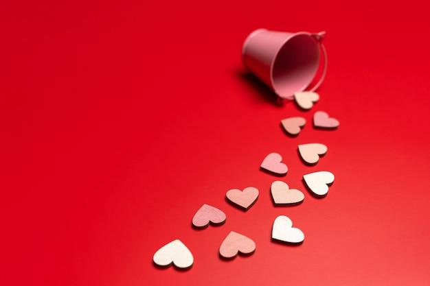 Kreatywne płaskie układanie obiektów w kształcie serca na jasnoczerwonym tle spadających z różowego wiadra. koncepcja miłości