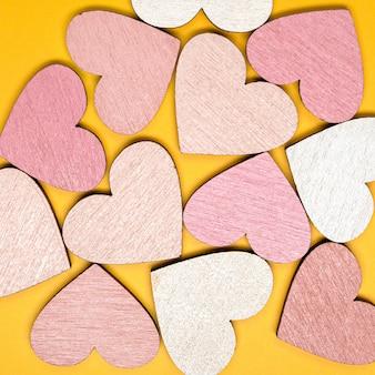 Kreatywne płaskie układanie obiektów w kształcie serca na jasnożółtym tle. koncepcja miłości.