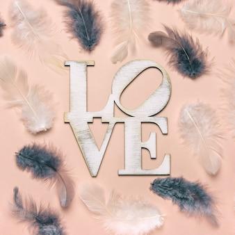 Kreatywne płaskie układanie słowa miłość z naturalnym piórkiem.