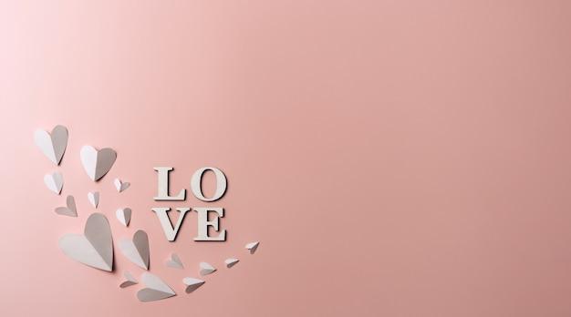 Kreatywne, płaskie ukształtowanie słowa miłość na miękkiej ścianie z papierowymi sercami.
