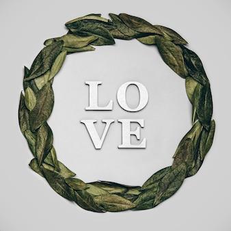 Kreatywne płaskie ukształtowanie słowa miłość na szarym tle z naturalnymi liśćmi.