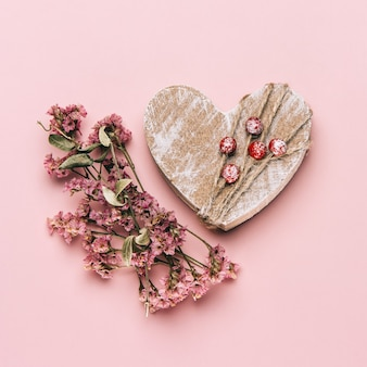 Kreatywne, płaskie ułożenie drewnianego serca na delikatnym kolorowym tle z naturalnymi roślinami.