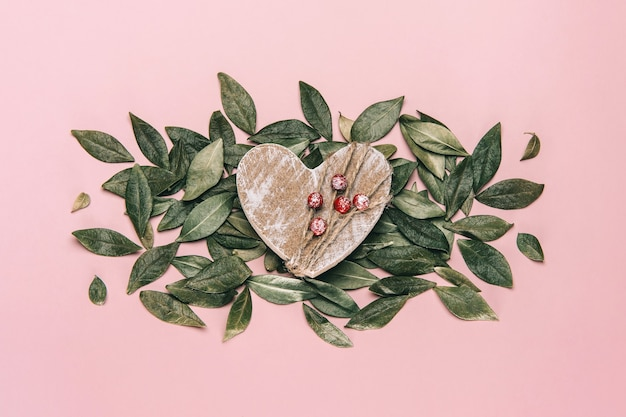 Kreatywne, płaskie ułożenie drewnianego serca na różowo z naturalnymi liśćmi.