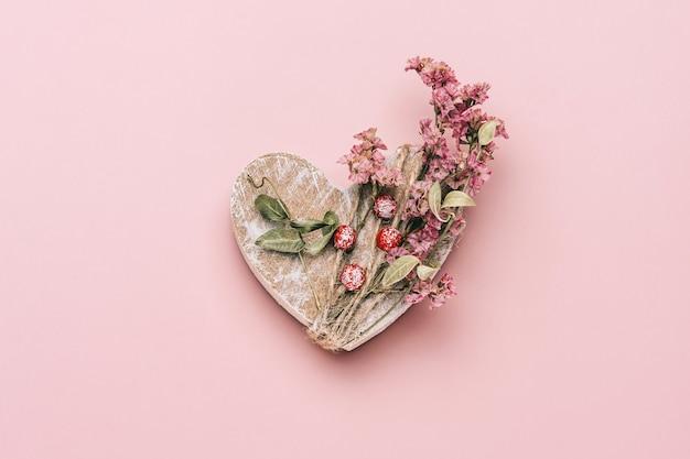 Kreatywne, płaskie ułożenie drewnianego serca na różowo z naturalnymi roślinami.