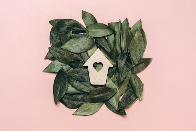 Kreatywne, płaskie ułożenie drewnianego węża z beżowym sercem z naturalnymi liśćmi.