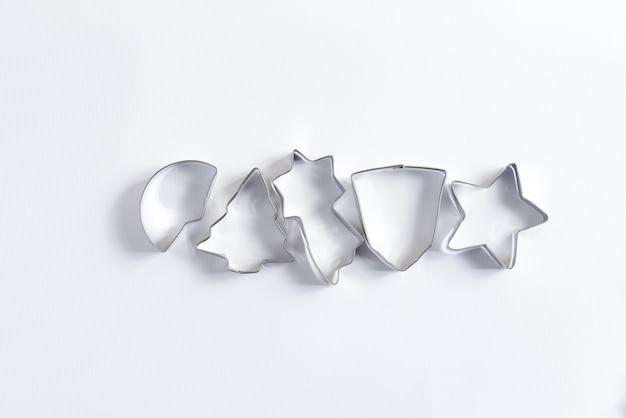 Kreatywne płaskie ułożenie ozdobnych metalowych foremek do gotowania domowych ciast bożonarodzeniowych na białym tle