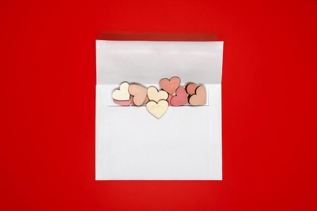 Kreatywne, płaskie ułożenie papierowej koperty z sercami na jasnoczerwonym tle. koncepcja miłości