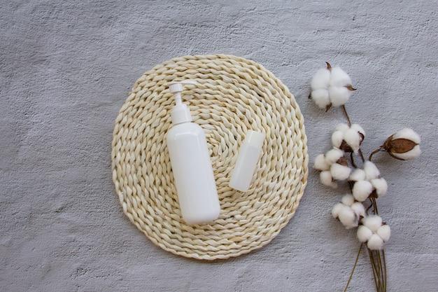 Kreatywne płaskie ułożenie plastikowej butelki z bawełnianymi kwiatami na podkładce z wikliny
