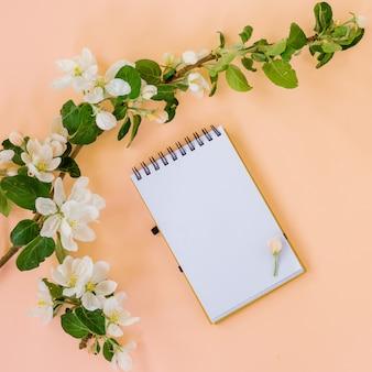 Kreatywne płaskie ułożenie pustej spirali notatnik rama makiety i płatki kwiatów jabłoni na pastelowym różowym tle z kopią miejsca w minimalistycznym stylu, szablon napisu, tekst lub projekt.