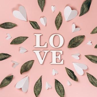 Kreatywne, płaskie ułożenie słowa miłość na miękkiej ścianie z naturalnymi liśćmi i papierowymi sercami.
