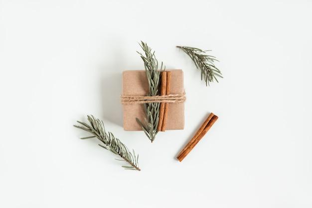 Kreatywne, płaskie ułożenie świątecznego pudełka prezentowego na ręcznie robionym brązowym pudełku z gałązką choinki i laskami cynamonu. kompozycja świąteczna.