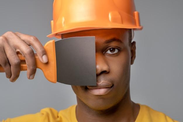 Kreatywne podejście. przystojny młody ciemnoskóry mężczyzna w pomarańczowym hełmie ochronnym, trzymając łopatkę na wysokości oczu