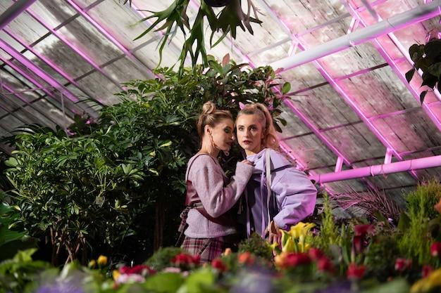 Kreatywne pomysły. atrakcyjne młode kobiety stojące razem wśród roślin podczas stylowej sesji zdjęciowej
