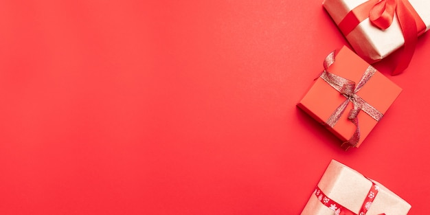 Kreatywne prezenty lub prezenty pudełka ze złotymi kokardkami i star konfetti na czerwony widok z góry. kompozycja płasko świecka na urodziny, święta lub ślub.