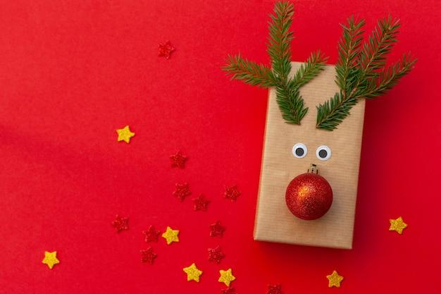 Kreatywne pudełko na prezent bożonarodzeniowy w postaci jelenia na czerwonym tle. karta z pozdrowieniami świątecznymi.