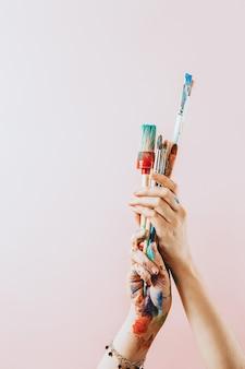 Kreatywne różowe tło. artystka ręka trzyma kolorowe pędzle. farby i pędzle tła. klasa plastyczna, szkoła plastyczna. koncepcja wyobraźni i kreatywność.
