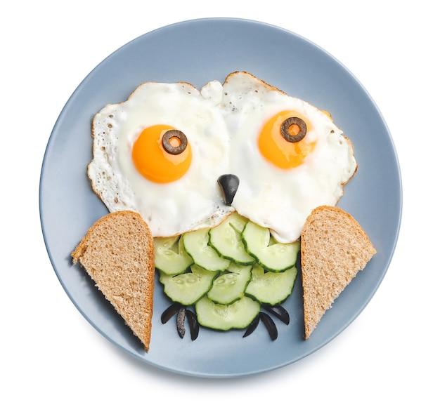 Kreatywne śniadanie dla dzieci z jajkami, tostami i świeżymi warzywami na białej powierzchni
