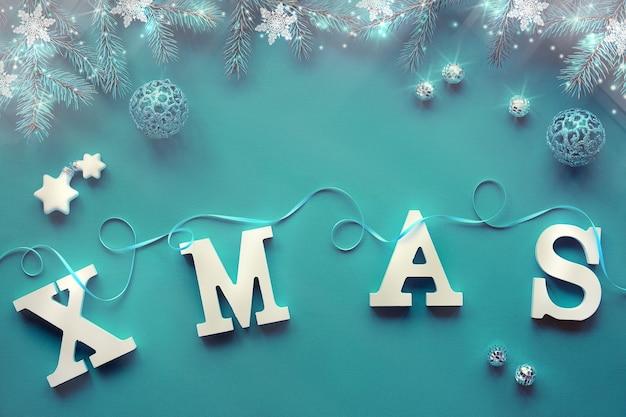 Kreatywne świąteczne mieszkanie leżało z dużymi literami xmas na zielonym obrusie tekstylnym ze srebrnymi dekoracjami. miętowo-zielone i białe bibeloty, błyszczące bombki i płatki śniegu na jodłowych gałązkach.